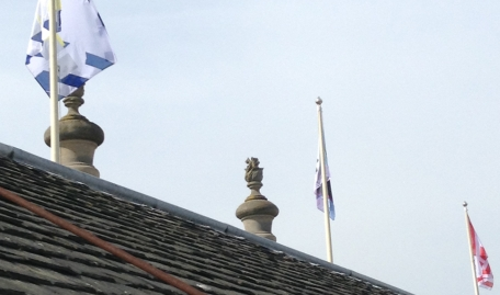 A view from the roof looking up at 3 of the new flags